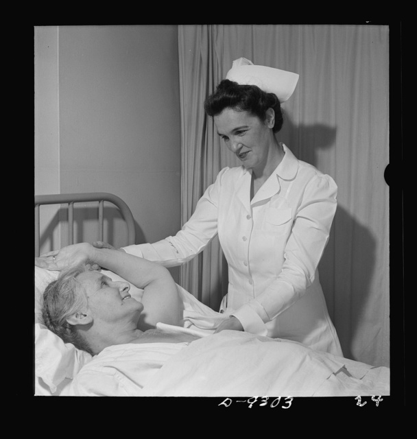 Nurse training. Post-operative care of patients is part of every nurse's responsibility. This nurse is showing a patient, recovering from a mastectomy, how to exercise her arm properly