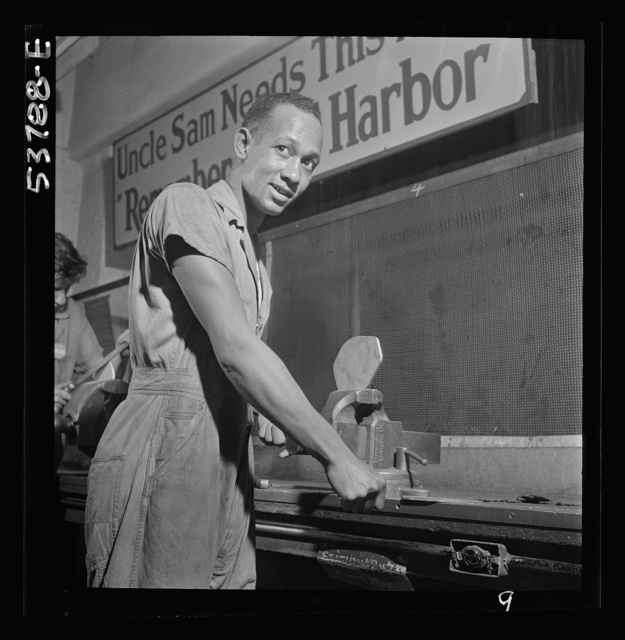 NYA (National Youth Administration) work center, Brooklyn, New York. A Negro bench worker, who is receiving training in machine shop practice, removing the burrs from a side piece for a metal pulley block