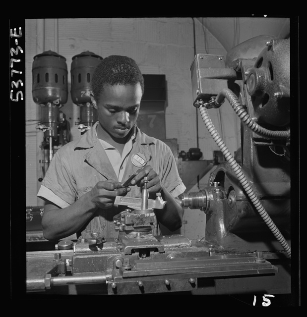 NYA (National Youth Administration) work center, Brooklyn, New York. A Negro bench-lathe worker, who is receiving training in machine shop practice, gauging a screw just removed from the collet