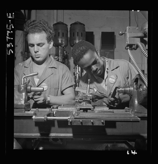 NYA (National Youth Administration) work center, Brooklyn, New York. Two bench-lathe workers, who are receiving training in machine shop practice, removing burrs from special taper head screws