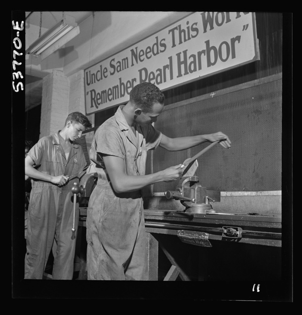 NYA (National Youth Administration) work center, Brooklyn, New York. Two bench workers, who are receiving training in machine shop practice, removing the burrs from a side piece for a metal pulley block
