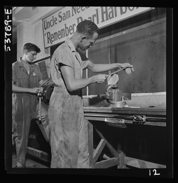 NYA (National Youth Administration) work center, Brooklyn, New York. Two bench workers, one white and one a Negro, who are receiving training in machine shop practice, removing the burrs from a side piece for a metal pulley block