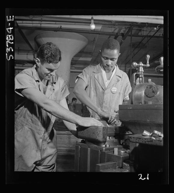 NYA (National Youth Administration) work center, Brooklyn, New York. Two men, white and Negro, who are receiving training in machine shop practice, shown setting up shaper work to cut forty-five degree angles at base for surface gauge