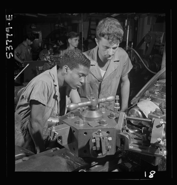 NYA (National Youth Administration) work center, Brooklyn, New York. Two turret-lathe workers, Negro and white, who are receiving training in machine shop practice, watching a cutting-off operation on a turret lathe