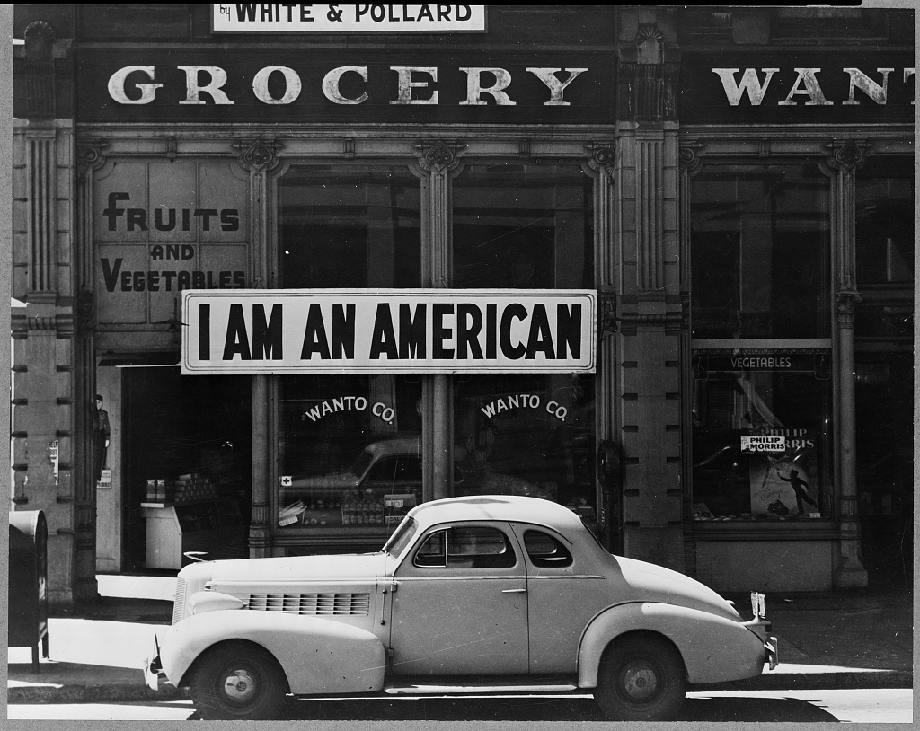 """Oakland, Calif., Mar. 1942. A large sign reading """"I am an American"""" placed in the window of a store, at 13th and Franklin streets, on December 8, the day after Pearl Harbor. The store was closed following orders to persons of Japanese descent to evacuate from certain West Coast areas. The owner, a University of California graduate, will be housed with hundreds of evacuees in War Relocation Authority centers for the duration of the war"""