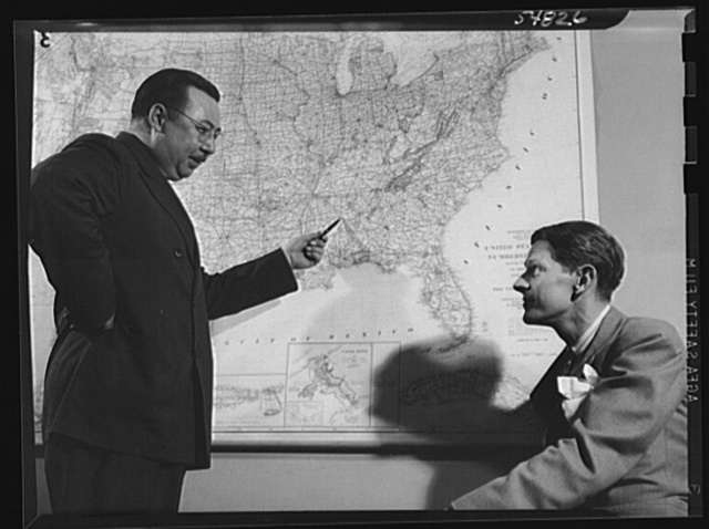 ODT (Office of Defense Transportation) system of port control. Henry F. McCarthy, director of the Division of Traffic Movement (right), discusses a prospective bottleneck development with assistant director Arch G. Warren, head of the Traffic Channels Section