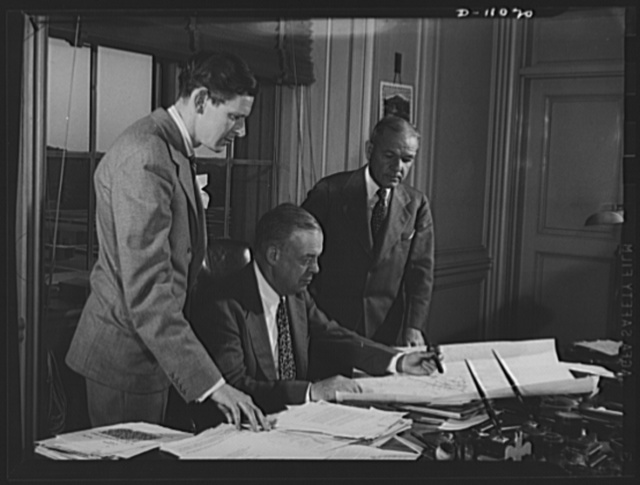 ODT system of port control. Joseph B. Eastman, Defense Transportation director (seated), checks a traffic channels map with Henry F. McCarthy (left), director of the Division of Traffic Movement, and V.V. Boatner, director of the Division of Railway Transport. These maps, changed daily, show nation-wide railway traffic conditions
