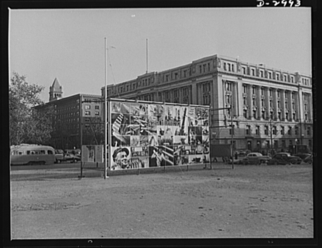"""OEM exhibit panel. Office of Emergency Management exhibit panel on display at 14th Street and Pennsylvania Avenue, Washington, D.C., November 1941. The panel was designed by Jean Carlu and executed by the Division of Information, OEM. One side depicted  in a photo-montage, """"The Four Freedoms."""" The other side described pictorially our """"Arsenal of Democracy"""""""