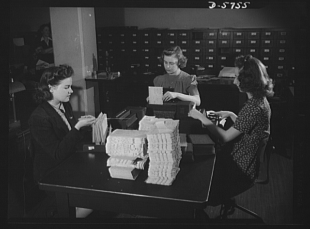 Office equipment used by the War Production Board (WPB). Girls operating a card punching machine for the machine tools section of the WPB. The cards show tools on order, delivery date promised, name of purchaser, and other information concerning the progress of machine tool production