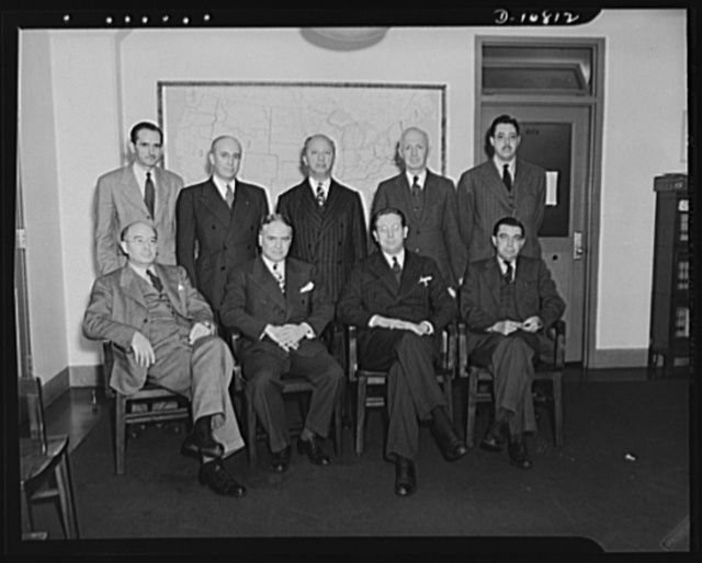 Office of Price Administration Regional Administrators. Regular meeting of OPA Regional Administrators in Washington, D.C., October 14th and 15th, 1942. Standing, left to right: Maxwell McCullough, Dallas, Texas; Clem W. Collins, Denver, Colorado; Harry F. Camp, San Francisco, California; Birkett Williams, Cleveland, Ohio; Oscar Strauss, Atlanta, Georgia. Seated, left to right: John C. Weigel, Chicago, Illinois; Sylvan Joseph, New York, New York; John E. Hamm, Senior Deputy Administrator, Washington, D.C.; Kenneth B. Backman, Boston, Massachusetts