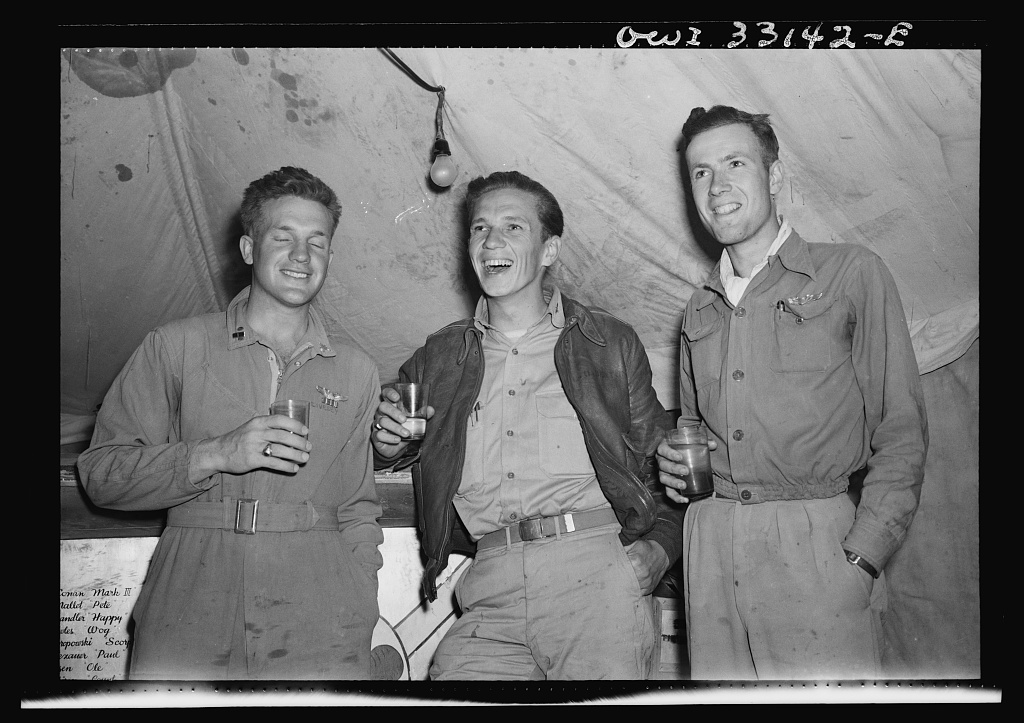 """Officer Bill Livesay, 25, Madison, New Jersey, (left) who accounts for three and one half enemy planes destroyed. Lieutenant John Stefanik, 24, Chicopee, Massachusetts, (left) who destroyed three enemy planes, and Lieutenant Charles Leaf, 21, South Orange, New Jersey, who destroyed two enemy planes in aerial victory over Sicilian straits. They are wearing the insignia of the 66th squadron of the 57th Fighter Group. This """"Squadron X"""" (for exterminators) made the high score of ther aerial victory with"""