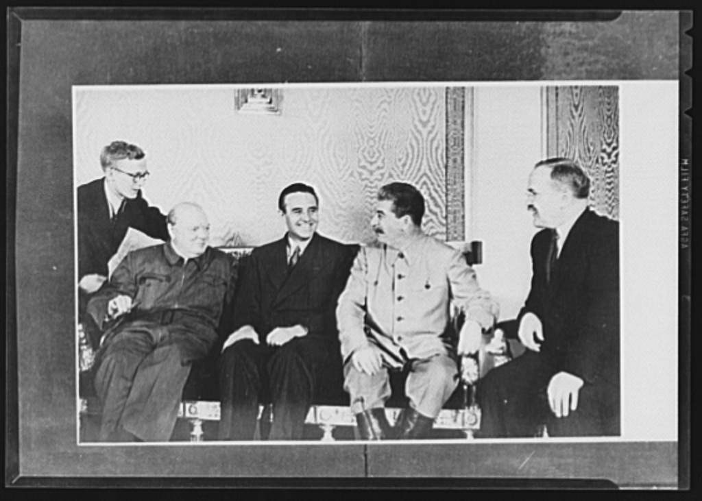Official pictures of meeting of Stalin, Churchill, Harriman. These are the first official pictures released in the United States of the recent meetings of Premier I.V. Stalin, Union of Soviet Socialist Republics; Prime Minister Winston Churchill of Britain; and W. Averrell Harriman, representing President Roosevelt. The three men met in the middle of August, 1942, at the request of the Soviet leader, and held a series of conversations concerned with the future conduct of the war. Also present was V.M. Molotov, Peoples' Commissar for Foreign Affairs, Union of Soviet Socialist Republics. The meetings lasted four days. Left to right, seated: Churchill, Harriman, Stalin and Molotov at the Kremlin. Unidentified man standing was the interpreter
