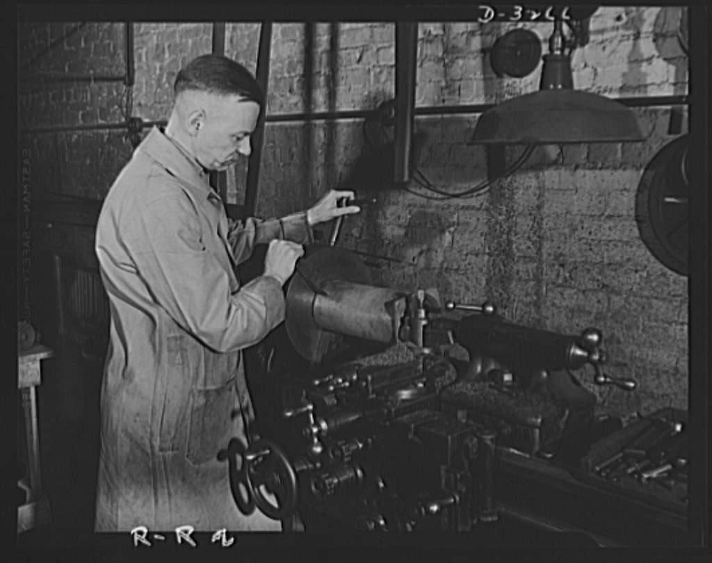 Oil burners to machine gun parts. Oil burners are the normal product of this Eastern factory now undergoing conversion to production of small precision parts for machine guns. This milling machine has not yet been converted to the war effort and is still turning out parts for burners. Reif-Rexoil Company, Buffalo, New York