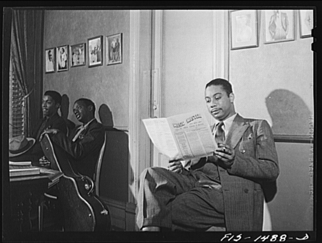 Oliver Coleman in the waiting room at Musicians' Hall, headquarters of local 208 of the musicians' union. He is waiting to see the president. Also waiting are, left to right:  Arthur Harrod and Alvin Bowen, two other members of the union. Mr. Coleman is reading Music Master, the official publication of local 208. Chicago, Illinois