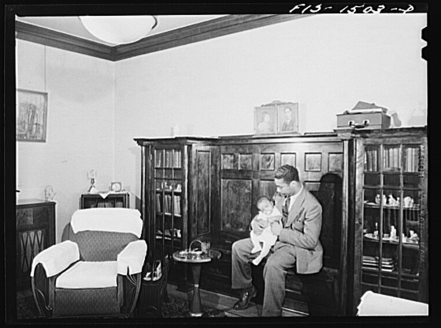 Oliver Coleman with his five-month-old son in the living room of his apartment on Indiana Avenue. Chicago, Illinois