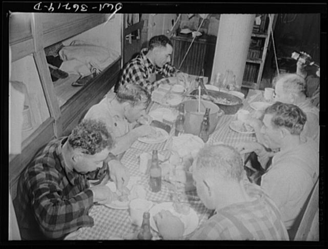 On board a fishing vessel out from Gloucester, Massachusetts. Crew eating in the forecastle. The one room serves as dining room, bedroom and kitchen. Between times the men use it for a game room, where they play cards and discuss politics