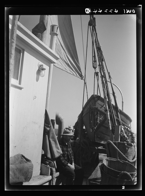 On board a fishing vessel out from Gloucester, Massachusetts. The power house, a riding sail, marker bouys, and canvas baskets