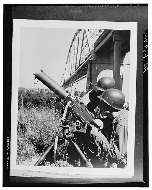 On the alert against attacking planes is this heavy machine gun crew, their weapon set up near a vital bridge in the Second Army's middle Tennessee maneuver area. The bridge was attacked three times by fast-striking dive bombers during a recent phase of the maneuvers. The gun is manned by Private Robert Hutcheson (gunner) of Red Bay, Alabama, and Private Virgil Lorence (assistant gunner) of Lucern, Missouri