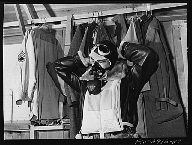 """One of the """"Flying Sergeants"""" dons his oxygen apparatus for high altitude flying. Immediately over his heavy flying suit is his """"Mae West"""" life preserver, which is easily inflated. Lake Muroc, California"""