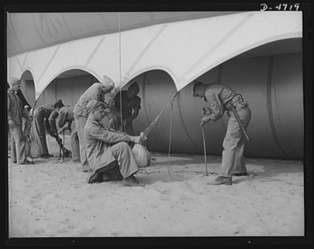 """Parris Island. Marine Corps barrage balloons. Bedding down a big barrage balloon is just another job that the leathernecks take in stride as special marine units are trained at Parris Island, South Carolina. """"Purging"""" it with fresh gas before it goes aloft again and running it up into a tactical formation under control of a steel cable are other features of a technique at which the marines have become very proficient"""