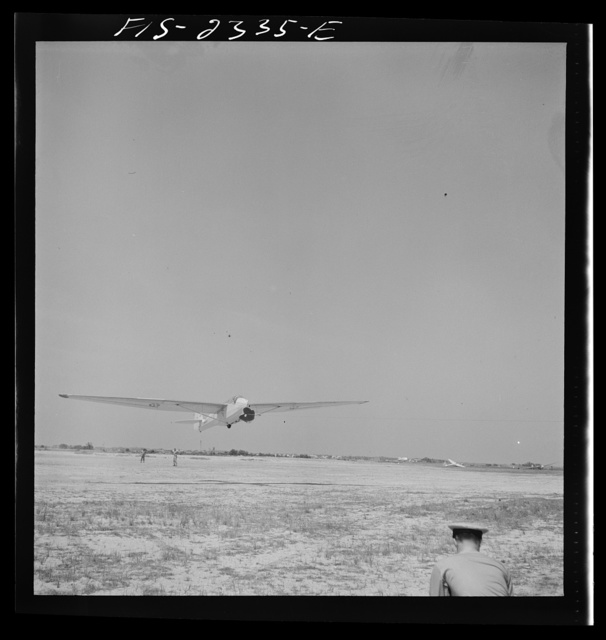 Parris Island, South Carolina. A glider plane being towed over a field at the U.S. Marine Corps glider detachment training camp
