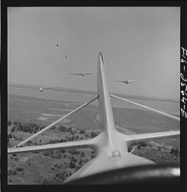 """Parris Island, South Carolina. U.S. Marine Corps glider detachment training camp. An aerial """"tug boat"""" tows three gliders high above the field"""