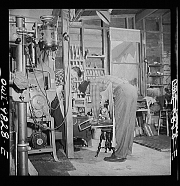 Passaic, New Jersey. Factory owner Carlson organized home machine shops for defense work. Helpers of a home machine shop owner. The piano stool serves as a horse