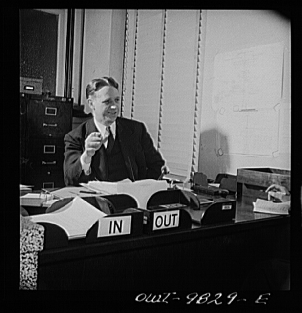 Passaic, New Jersey. Factory owner Carlson organized home machine shops for defense work. Carlson at his desk in the Washington WPB office where he worked several days a week