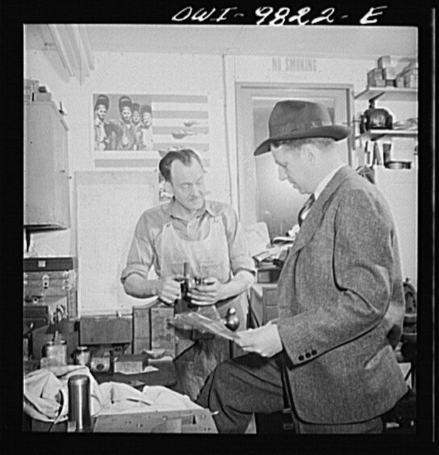 Passaic, New Jersey. Factory owner Carlson organized home machine shops for defense work. Carlson examining blueprints
