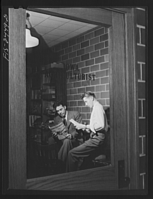 """Paul Visser, left, retiring editor of the """"Iowa Agriculturist"""" and Merle Hunt, business manager, discussing the last issue of the magazine, which is the campus publication of the agriculture students at Iowa State College. Paul is a senior in Animal Husbandry and Merle is a sophomore. Ames, Iowa"""