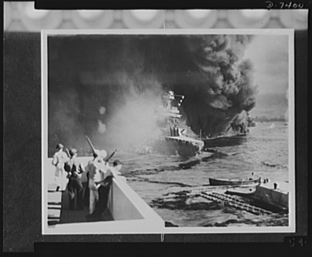 Pearl Harbor bombing. California hit. Battered by aerial bombs and torpedoes, the USS California settles slowly into the mud and muck of Pearl Harbor. Clouds of black, oily smoke pouring up from the California and her stricken sister ships conceal all but the hull of the capsized USS Oklahoma at the extreme right