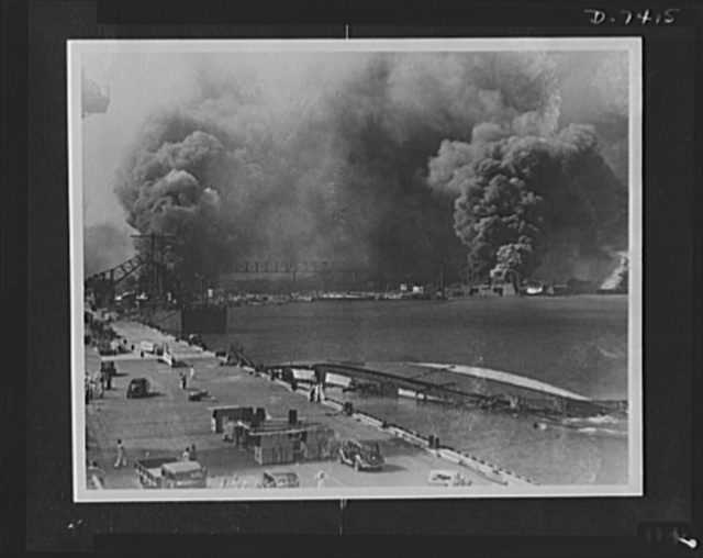 Pearl Harbor bombing. Destruction. Smoke pours from the USS Shaw, bombed dry dock (right center) while in the foreground lies the capsized USS Oglala, a minelayer. To the left is the 10,000 ton cruiser, USS Helena, struck by an aerial torpedo on the starboard side. The concussion caused the Oglala, formerly berthed alongside the Helena to flood and she turned over after being brought to dock. At the extreme left, may be seen some of the superstructure of the USS Pennsylvania and at the right appears to be the USS Maryland burning