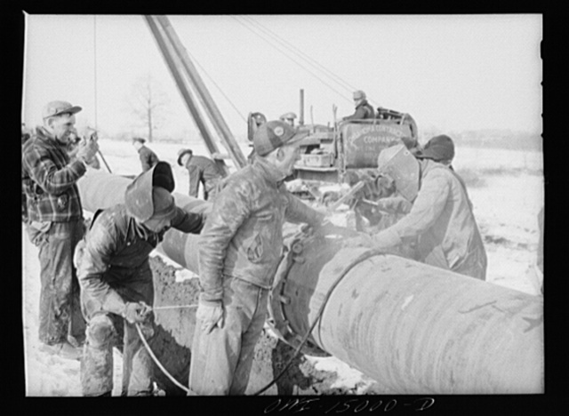 Pennsylvania section of the war emergency twenty-four inch pipeline to carry oil from Texas fields to eastern refineries, completed in July 1943. Tack welding a section of pipe to the main line