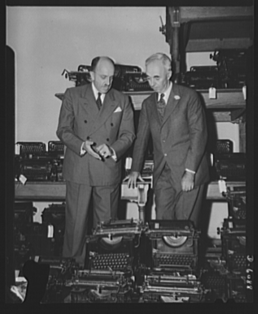 Phillip D. McCullough, left, with Metropolitan Life President Leroy S. Lincoln, looking over typewriters; part of a lot being sold to the government by the company today