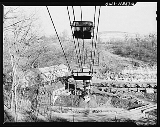 """Pittsburgh, Pennsylvania (vicinity). Montour no. 4 mine of the Pittsburgh Coal Company. Slate is loaded into separate cars in the mine and when the """"trips"""" come into the tripple, the slate is dumped onto a conveyor belt which dumps it into moving overhead cars which carry the refuse a mile up the hill where it is dumped"""