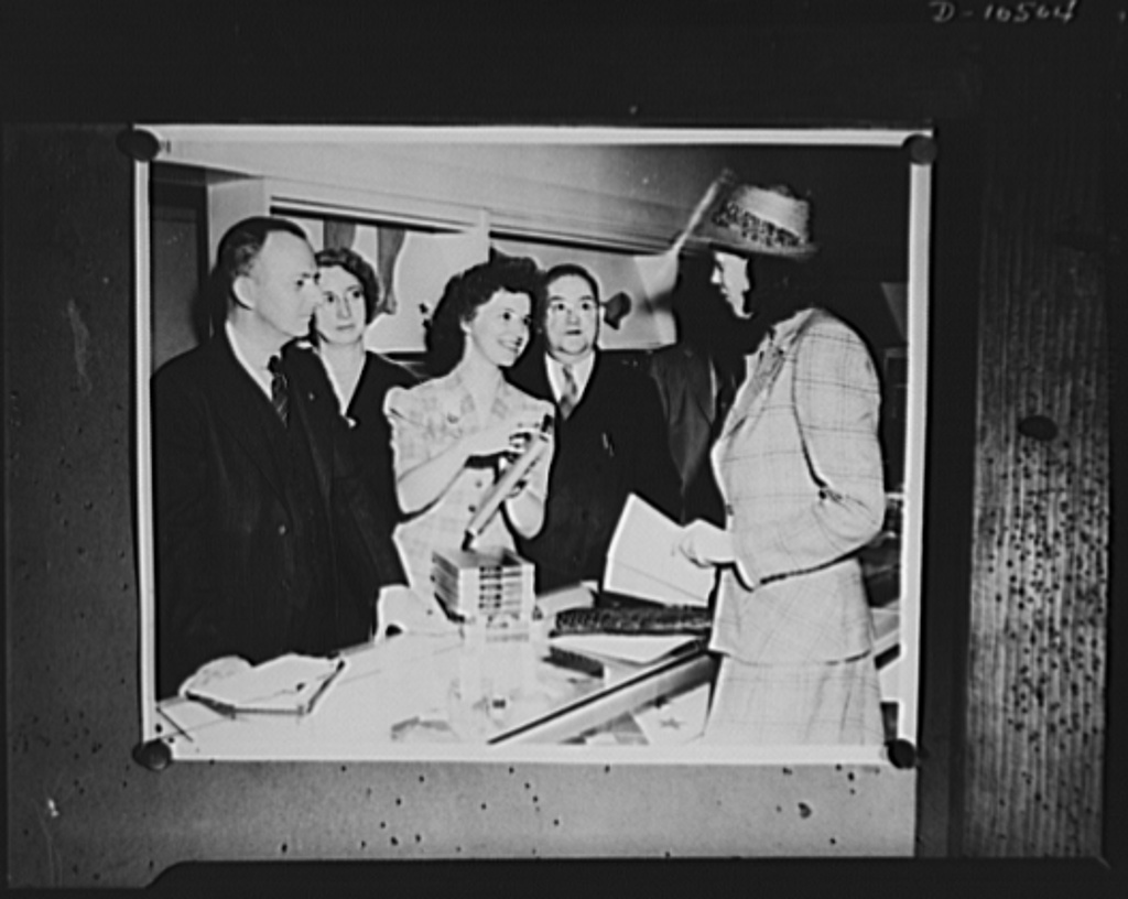 Posed photograph at a department store in Philadelphia, with volunteer woman investigator checking for Office of Price Administration's (OPA) enforcement agency prices of lingerie and hosiery