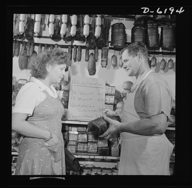 Posting ceiling prices in foreign languages. Anthony Weber, proprietor of a store in the German section of New York, is selling a Westphalian ham to Mrs. Elizabeth Freygang. The names are German, but both are patriotic Americans, glad to be in the United States, where a storekeeper is free to keep such well-stocked racks of food. Weber has shown his support of his adopted country by posting his ceiling price list