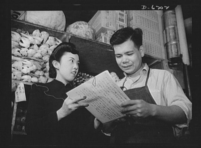 "Posting ceiling prices in foreign languages. Equipped with her ""bible,"" a copy of the General Maximum Price Regulations written painstakingly in Mandarin, one of the chief languages of China, Mrs. Joanne A. Tee, price specialist of the Office of Price Administration (OPA), is explaining the necessity for posting ceiling prices to Lee Bow, manager of a large wholesale and retail store in New York's Chinatown. Like the people of their native land, whose fighting spirit has earned the admiration of all freedom-loving nations, the Chinese-American storekeepers are fighting the Axis by cooperating with the government in the battle against inflation"