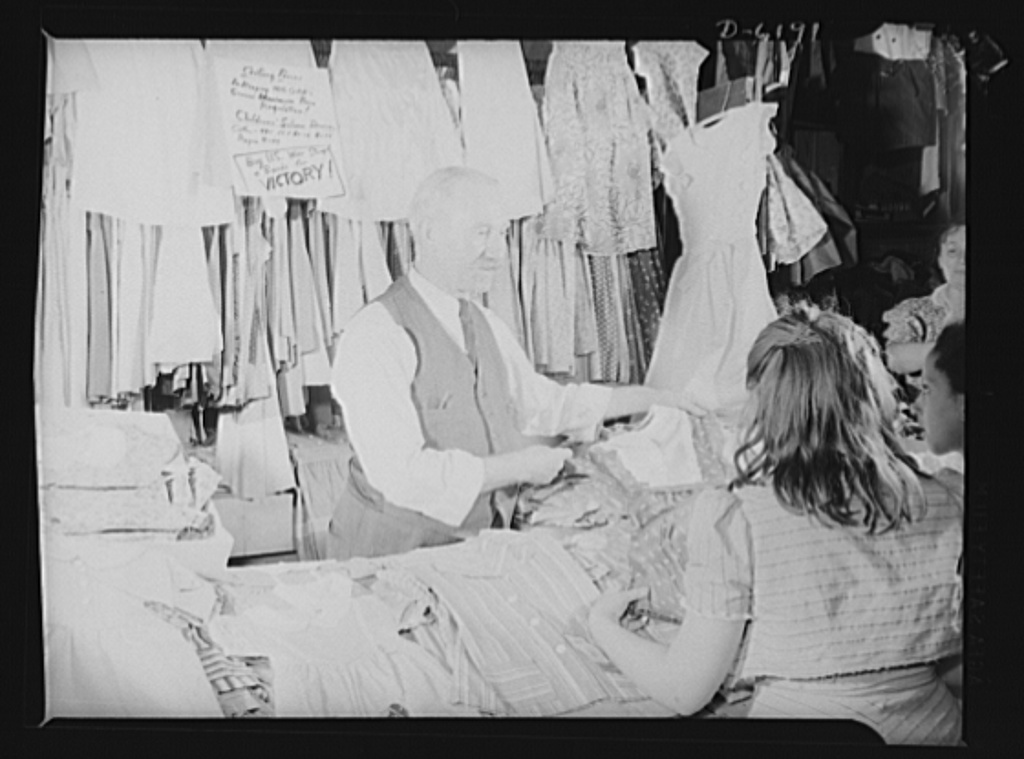 """Posting ceiling prices in foreign languages. The plea to """"Buy United States War Stamps and Bonds for Victory,"""" which completes the ceiling price sign, emphasizes the patriotic spirit shown by O. Schwartz, proprietor of a children's dress stand in one of New York's East Side marketplaces. Mr. Schwartz shows his desire to help his country by posting his maximum prices in cooperation with the government's fight against inflation"""