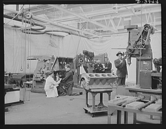 Preparing for tank production. A temporary machine shop is set up in a big automobile plant. A large drill press , a radial drill press, a vertical mill and a horizontal mill are background for an engine block of the type to be used in the tank motor. Ford Lincoln plant, Michigan