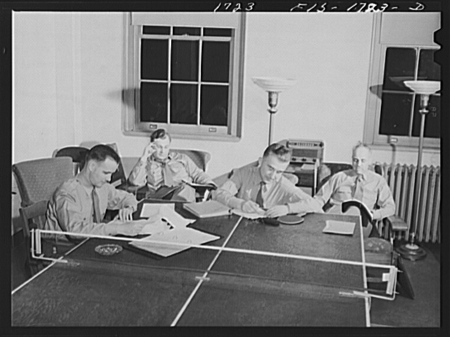 Preparing lessons for the next day's class in the recreation room of the U.S. Army chaplain school, Fort Benjamin Harrison, Indiana. Left to right, Chaplains F.J. O'Brien, George Brennan, P.L. Cronin and P.M. Hickcox