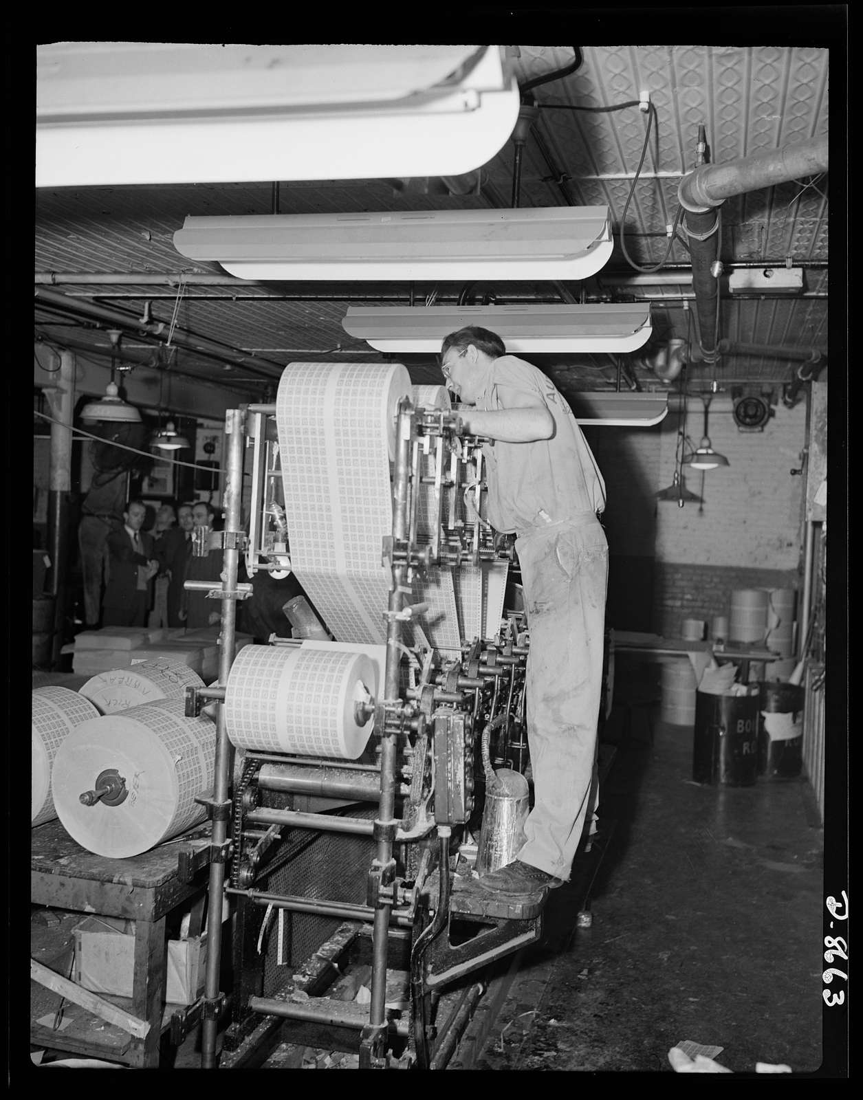 Printing war ration book 2. Another view of the collator with Otto Krantz checking the operation of the collating machinery. Note the glue can at his feet