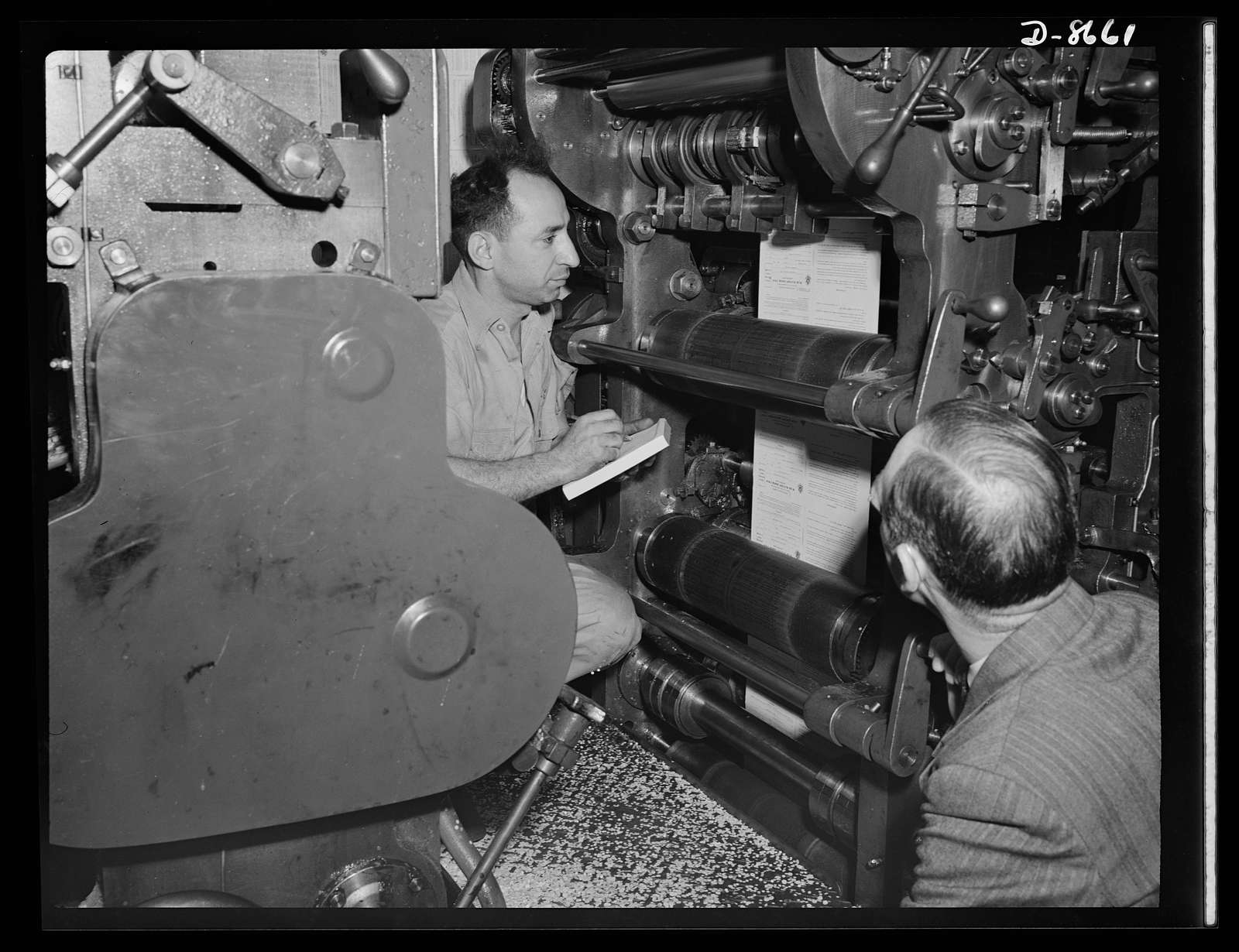 Printing war ration book 2. Covers for war ration book 2 roll from the press at a plant in Hoboken, New Jersey. The press is stopped as the ration book's serial number is checked