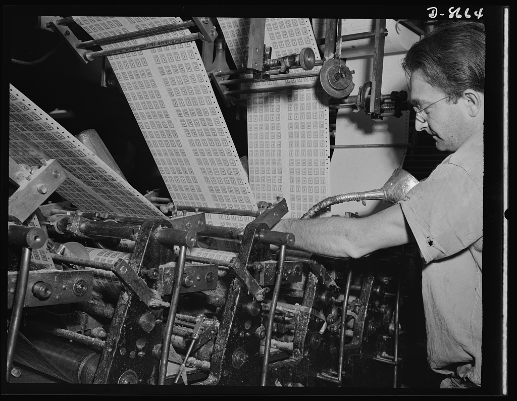 Printing war ration book 2. Otto Krantz replenishes the glue in the glass cylinders in the collator that supplies the glue for securing the coupon pages