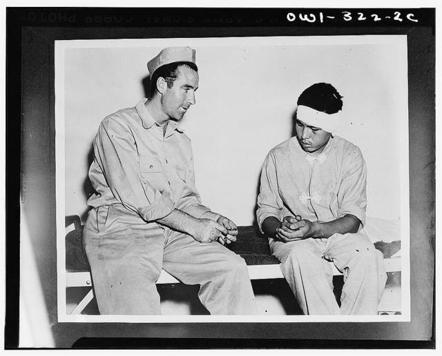 Private Henry F. Rourke shows a rosary to a wounded Jap soldier and learns that the latter is a Buddhist. Most of the captured Japs speak English, but they did little talking
