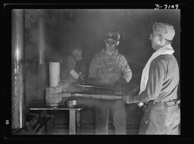Production. 105 millimeter shells. This red-hot billet is undergoing processing in a hydraulic press, where it will be pierced and drawn into the rough shape of an artillery shell. In pre-war days, plumbing fixtures were processed in this Midwest factory (Manitowac Shipyards)