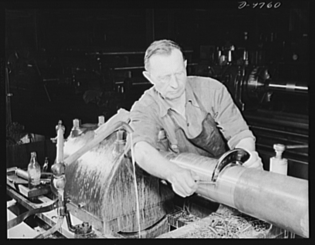 Production. 105 mm. howitzers. Adolph Pranewicz of Milwaukee, who has a son in the Marines, checking off rough material with a gauge after the first turning on a lathe of a 105 mm. howitzer at the plant of Chain Belt Company, Milwauke, Wisconsin