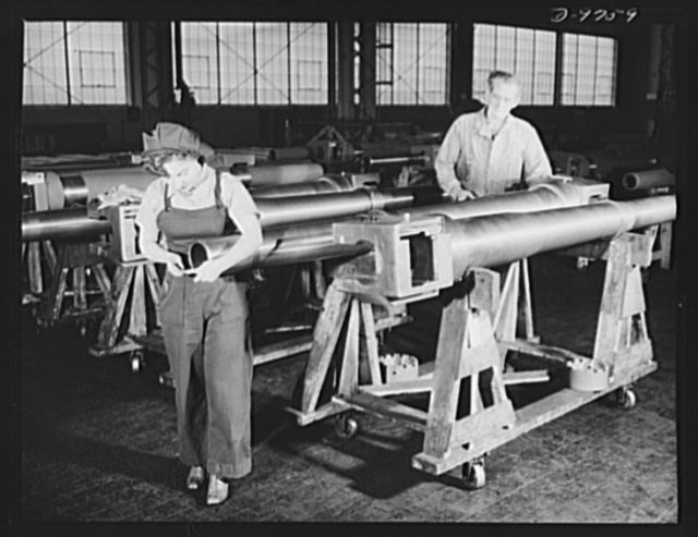 Production. 105 mm. howitzers. Dorothy Conger and Earl A. Ross, U.S. ordnance inspectors, checking over 105 mm. howitzers in the plant of Chain Belt Company, Milwaukee, Wisconsin