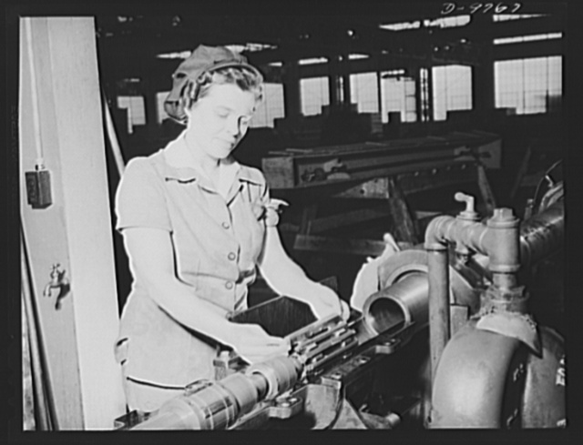 Production. 105 mm. howitzers. Lillian Goritschnig with two sons in the service, one overseas, and a husband ready to go into the service, inspecting the inside of a 105 mm. howitzer at the Milwaukee, Wisconsin plant of Chain Belt Company, with microbrand and also shot-changing the honing stone for finished inside operation of 105 mm. howitzers