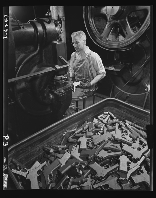 Production. 45-caliber pistols. John Ignacek pierces trigger hole guards on .45-caliber automatic pistols in the plant of a large manufacturer of firearms. The plant produces pistols, machine guns and other weapons that will soon be spreading trouble for the Axis. Many men and women are employed in this plant which produces pistols, machine guns and other essential weapons for the armed forces